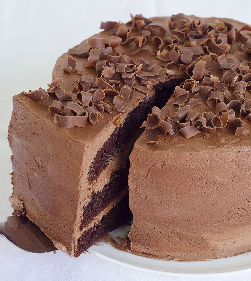Whole chocolate cake with one piece in the middle.
