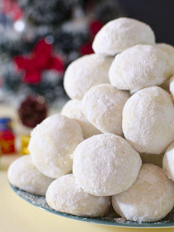 Bunch of Christmas Coconut Snowball Cookies on green plate