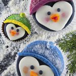 Three penguin cupcakes with colorful hats
