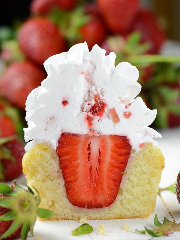 Half sliced Strawberry Shortcake Cupcake with a big strawberry .