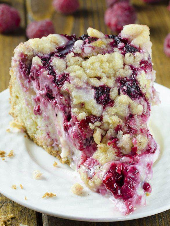 Slice of Raspberry Cream Cheese Coffee Cake on a white plate with a bunch of raspberry behind.