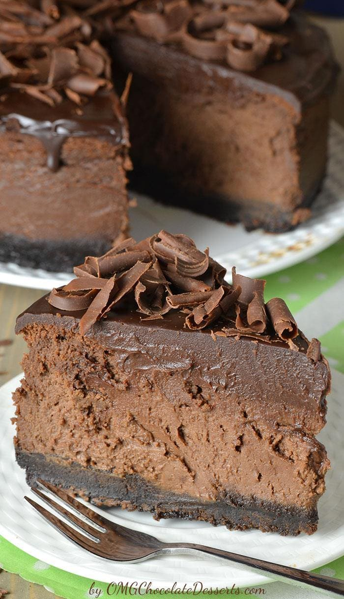 Decadent piece od Triple Chocolate Cheesecake on a whit plate with a whole cake behind.