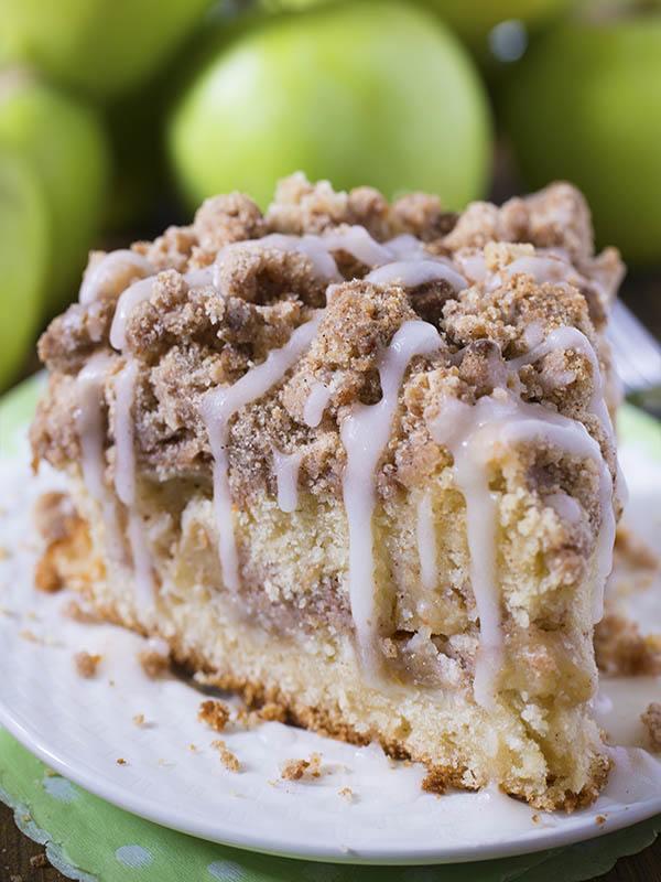 Piece of Cinnamon Apple Crumb Cake in front of bunch of apple.