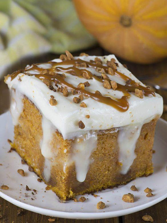 Pumpkin Poke Cake piece on a white plate with pumpkin behind.