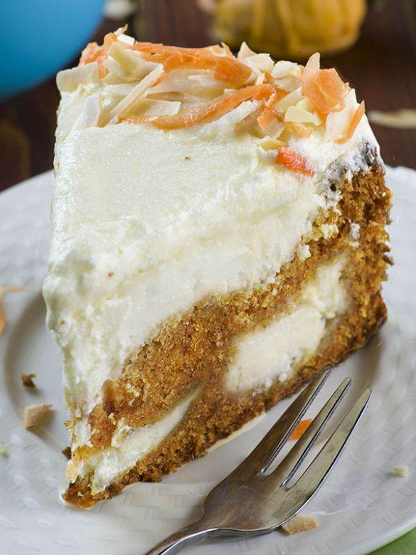 piece of Carrot Cake Cheesecake served on white plate.