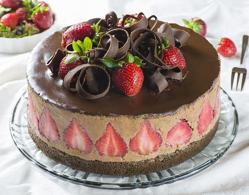 chocolate cake with chocolate covered strawberries on top