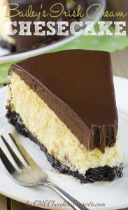 Piece of Irish Cream Cheesecake on a white plate and fork beside. Three layer cheesecake - ganache, golden cheesecake layer and black Oreo crust.