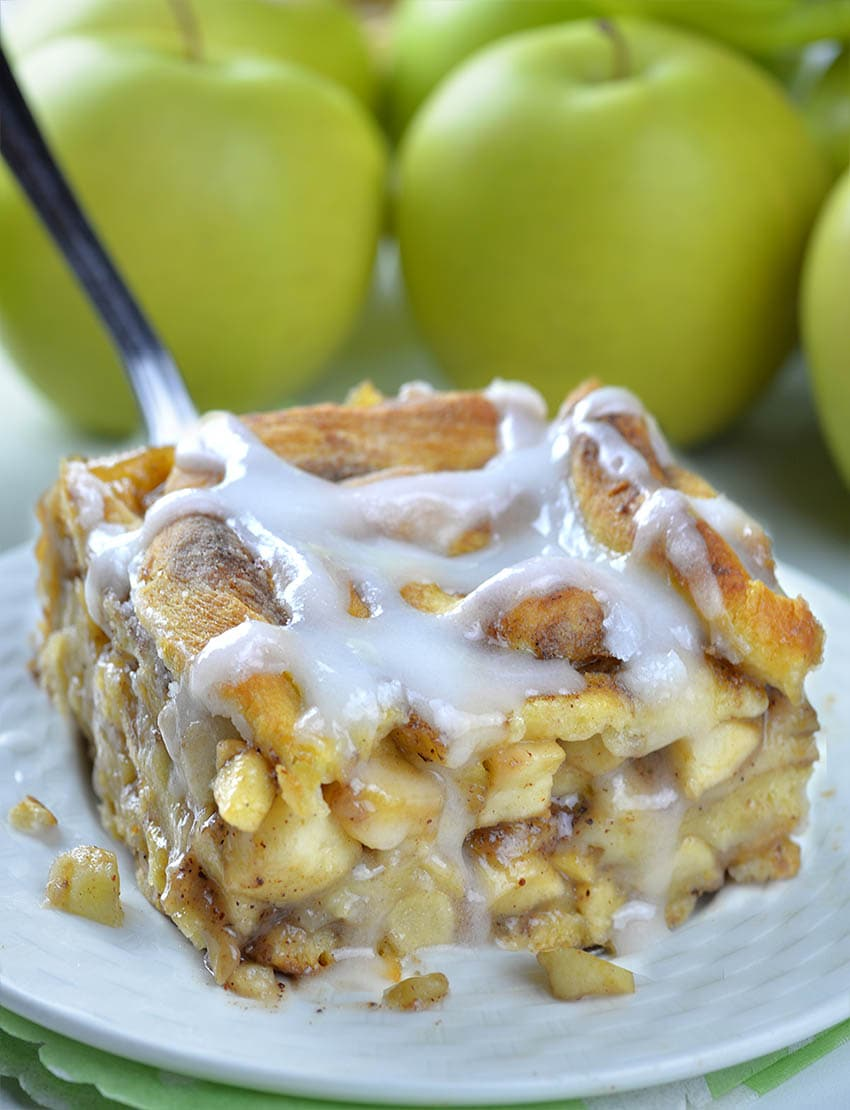 Caramel Apple Cinnamon Roll Lasagna piece on a white plate with couple of apples behind.