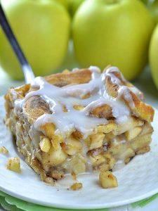 Piece of Caramel Apple Cinnamon Roll Lasagna on a white plate in front of bunch of apples.