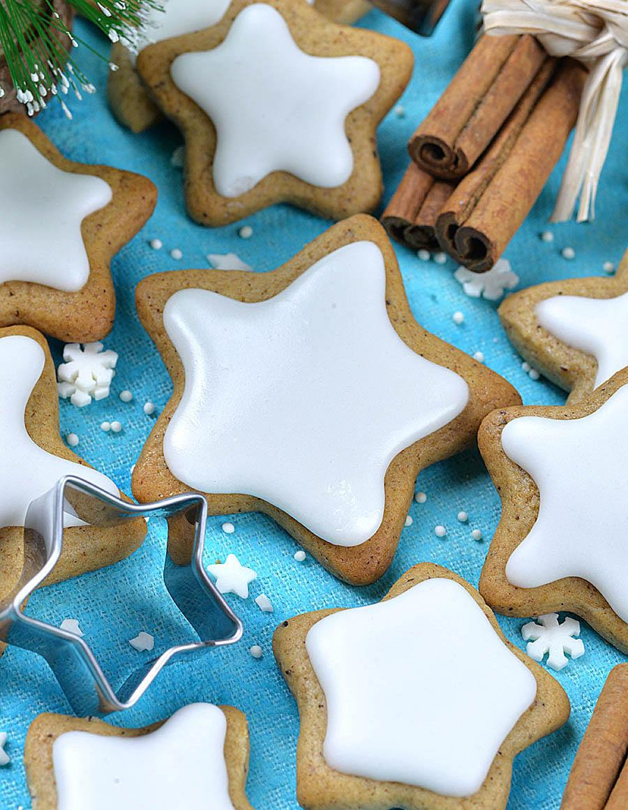 Star shaped cookies laying on the table with star cookie cutter.