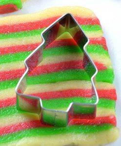 Christmas tree cookie cutter on three colors cookie dough.