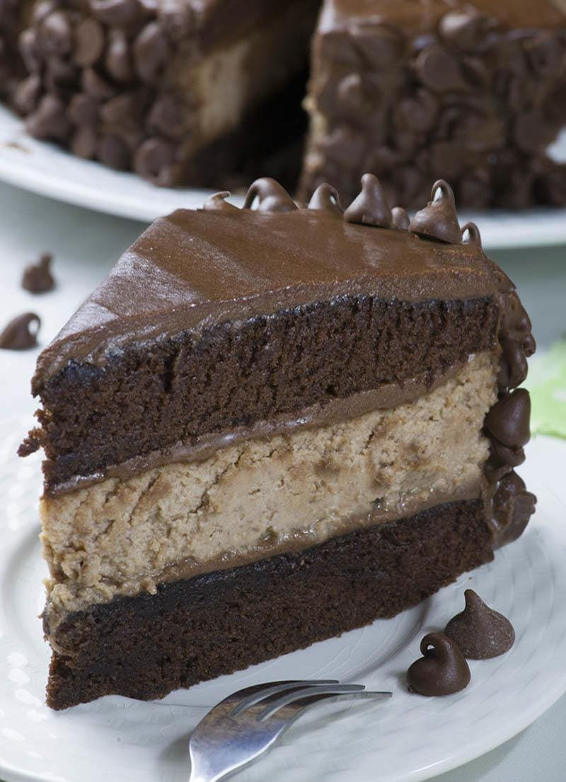 Piece of Hershey Cheesecake Chocolate Cake on a plate with whole cake behint them.