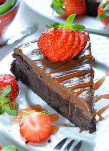 Piece of Flourless Chocolate Cake on a white plate garnished with strawberry.
