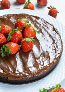 Whole Flourless Chocolate Cake with couple of strawberries.