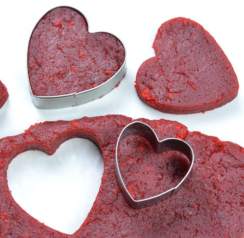 Red velvet cake dough with heart shaped cookie cutter.