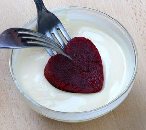 Heart shaped red velvet cake dough dipped into white chocolate.