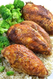 Three pieces of Healthy Slow Cooker Chicken Breasts on rice and broccoli.