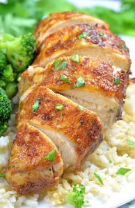 Cut piece of Healthy Slow Cooker Chicken Breast on a plate with rice.
