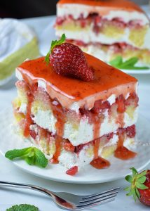 Piece of frozen strawberry shortcake dessert on white plate garnished with strawberry on top.