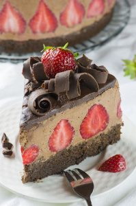 Piece of strawberry chocolate cake on a white plate. Chocolate layer with strawberries inside, garnished with chocolate curls and strawberries on top.