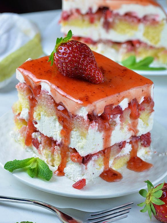 Strawberry Icebox Shortcake on white plate with strawberry on top.