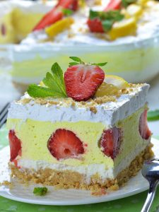 Big piece of Strawberry Lemonade Lasagna on a plate in front of casserole. Yo can see 4 gorgeous layers: bottom Golden Oreo layer, cream cheese layer, yellow lemonade layer with half cut strawberries and top whipped cream layer garnished with strawberries.