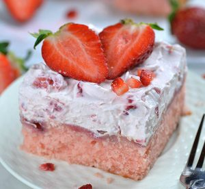 Strawberry sheet cake piece on a plate garnished with split strawberry.