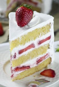 Piece of strawberry shortcake cake on a plate with garnished strawberries.