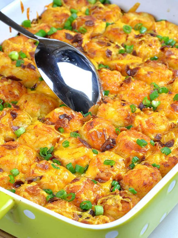 Tater Tot Breakfast Casserole with spoon and garnished with onion.