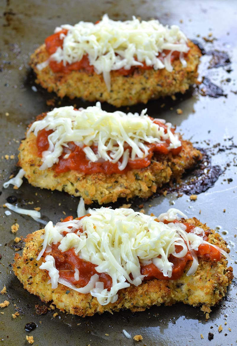 8e29c6799bf7 Three pieces of Baked Chicken Parmesan with marinara sauce on top