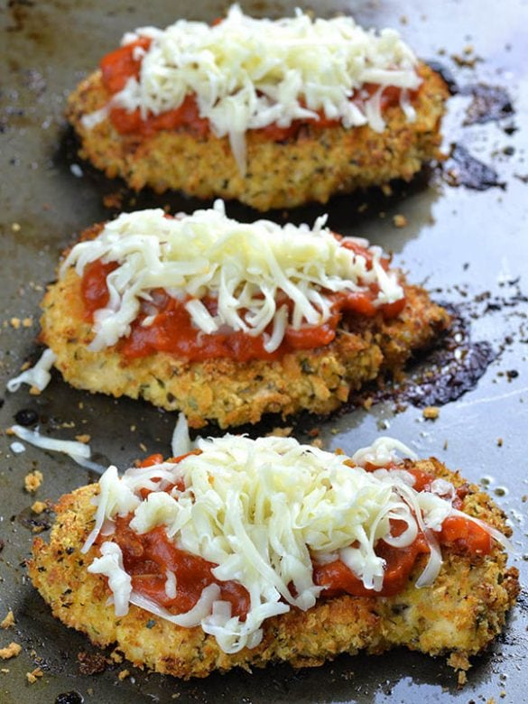 Three pieces of Baked Chicken Parmesan with marinara sauce on top, then sprinkle with shredded cheese