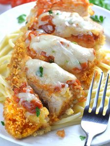 Whole piece of Baked Chicken Parmesan on a white plate laying on spaghetti with fork.