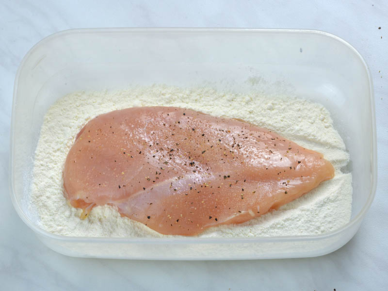 Chicken breast in half with season with salt, freshly ground black pepper and garlic powder laying on flour.
