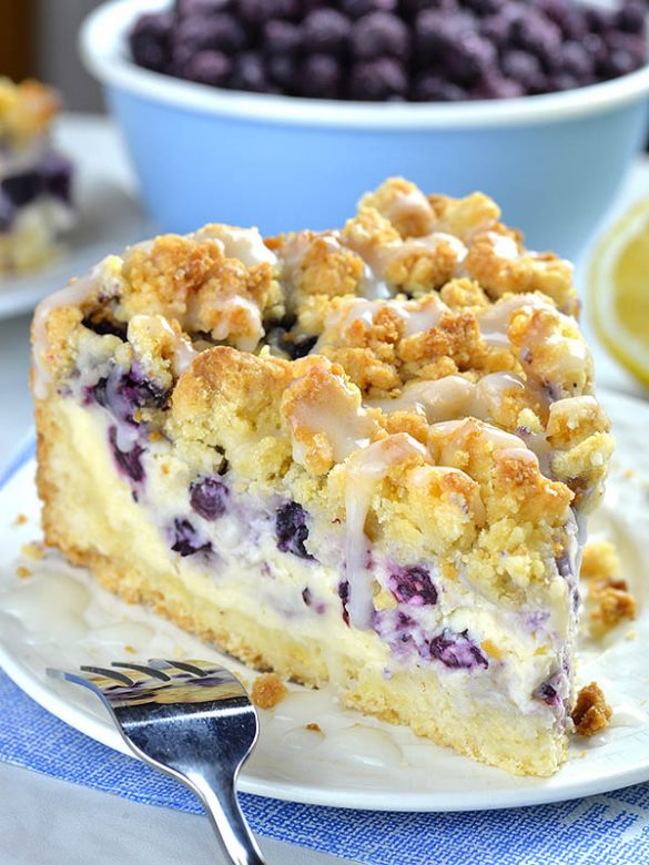 Piece of Blueberry Cheesecake Crumb Cake on a white plate in front of bowl full of fresh blueberries.