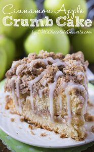 Piece of Cinnamon Apple Crumb Cake on a white plate with a bunch of apples behind.