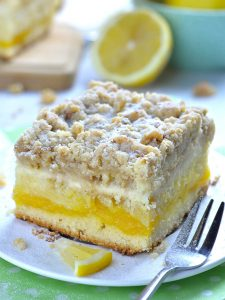 This tender and fluffy cake is super moist. It has a tart lemon curd layer in the center, cheesecake layer on top and irresistible, crunchy and buttery crumb topping!
