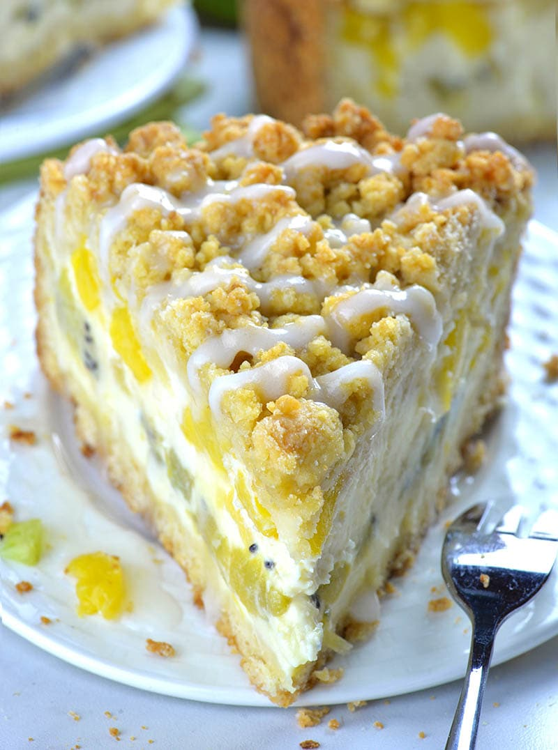 Piece of Tropical Fruit Cheesecake Crumb Cake on a white plate with fork behind them.