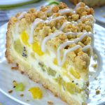 Slice of cheesecake crumb cake with kiwi, mango, and pineapple
