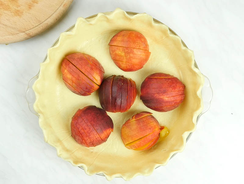 Unbaked pie dough with six peaches.