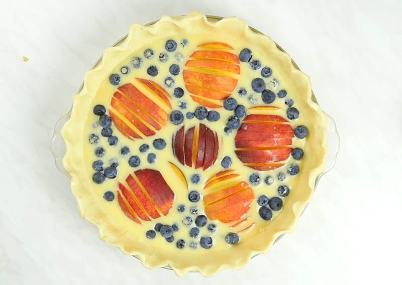 Unbaked pie dough with six peaches. with custard filled with blueberries.