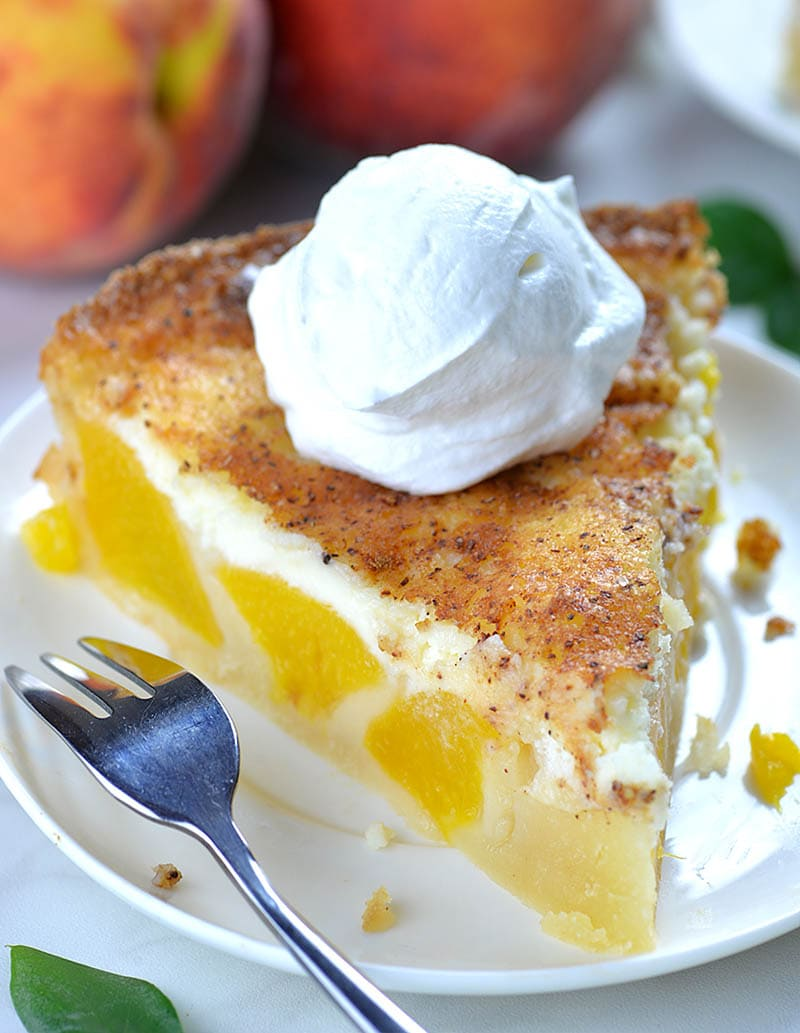 Piece of Peach and Cream Pie on a white plate garnished with whipped cream on top.