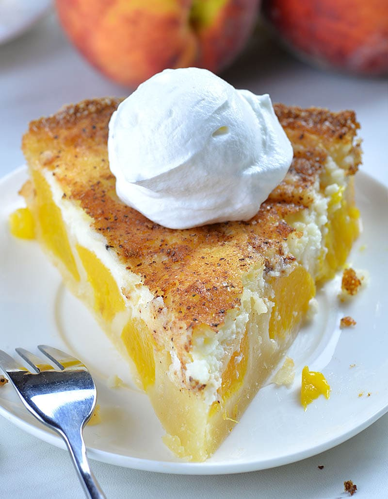 Front perspective of piece of Peach and Cream Pie on a white plate garnished with whipped cream on top.