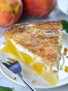 Piece of Peach and Cream Pie on a white plate.