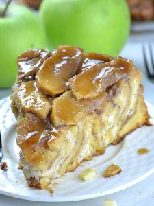 Piece of Upside Down Apple Cinnamon Roll Cake on a white plate with two apples behind.