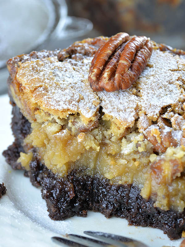 Chocolate Pecan Ooey Gooey Butter Cake with fudgey brownie layer at the bottom, ooey gooey pecan pie filling in the center and buttery cream cheese topping, hidden like molten lava under the amazing thin layer of sweet flakes