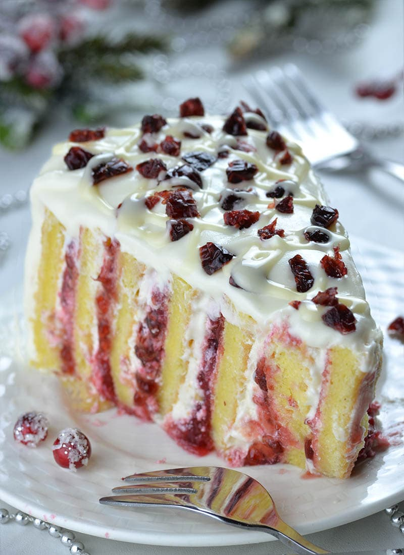 Piece of Christmas Cranberry Cake on a white plate with dry cranberries on top.