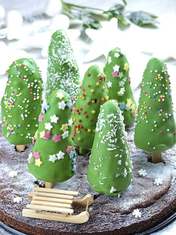 Christmas Tree Cheesecake on a stick on a chocolate cake in form of snow forest.