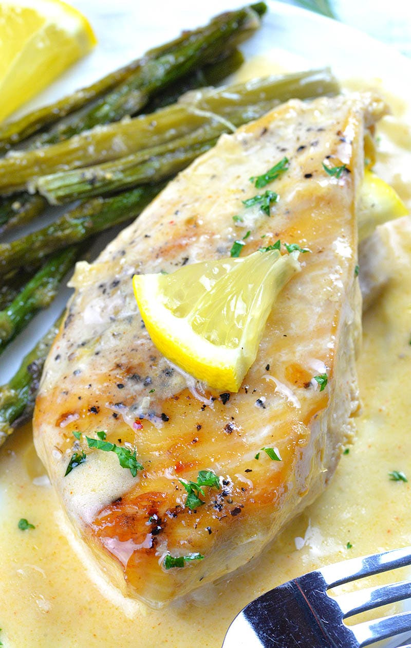 Big piece of chicken breast in creamy lemon sauce garnished with lemon.