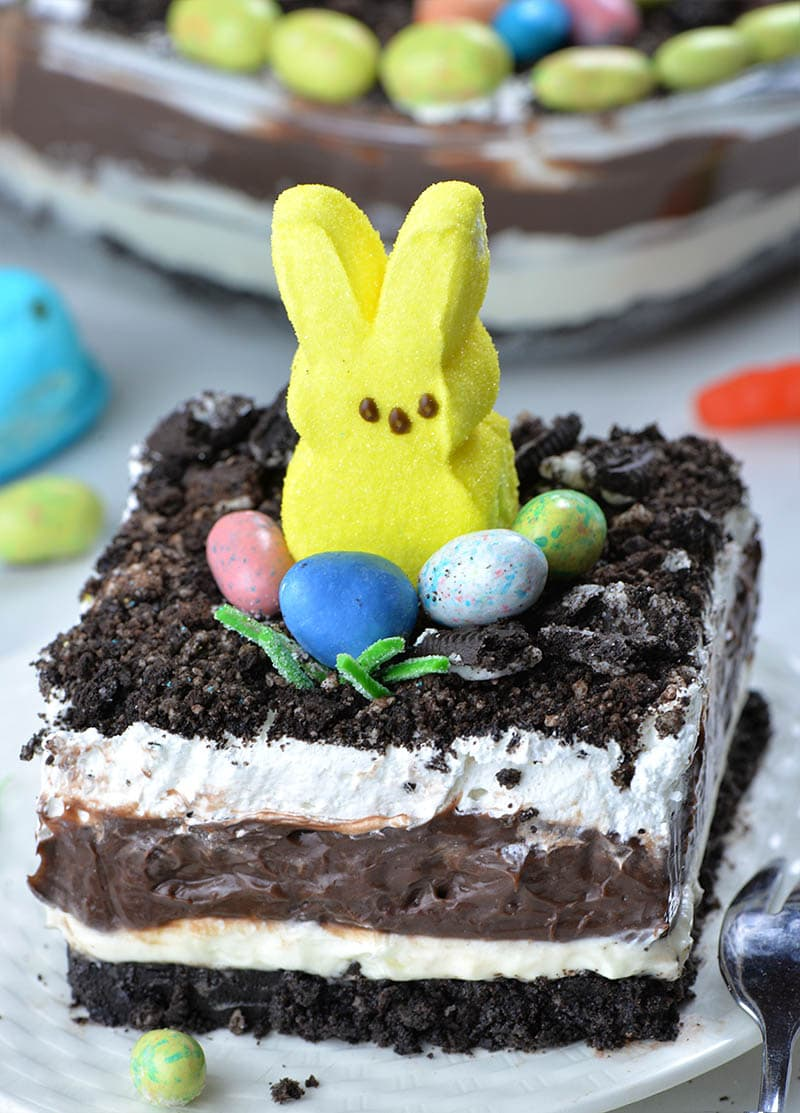 Four layered Easter Chocolate Lasagna garnished with Oreo dirt on top, Peeps Bunny and couple of Easter eggs candy.