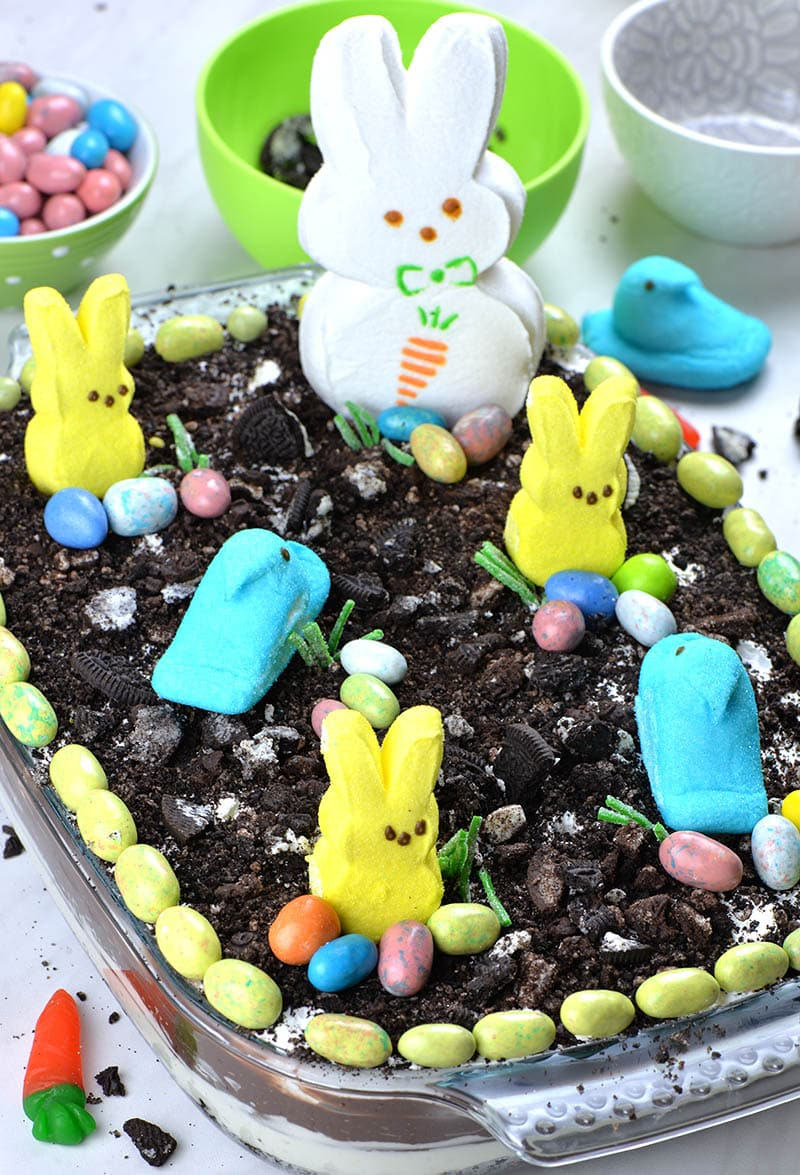 Easter Chocolate Lasagna in a pan! Three yellow Easter Peeps Bunnies, two blue chicks and one big white bunny with buns of Easter eggs candy.